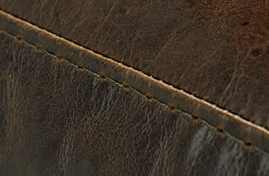 Close-up of stitching on dark brown leather sofa