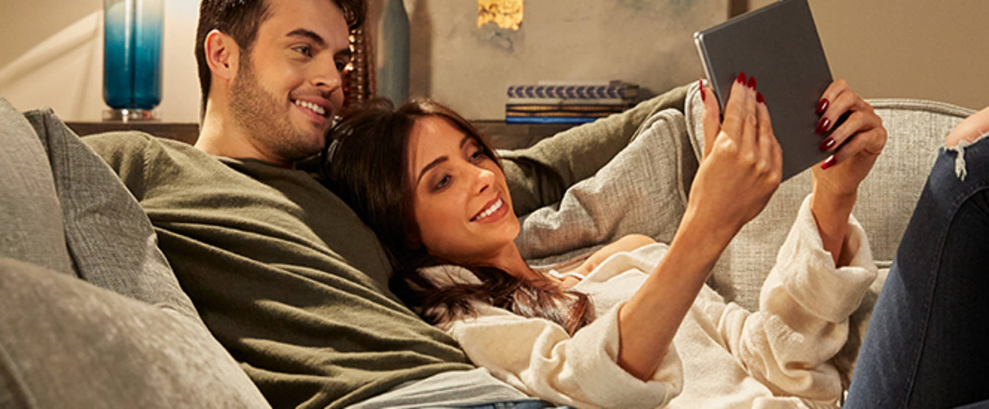 Couple relaxing of sofa looking at tablet