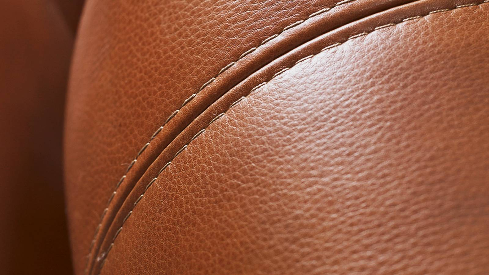 Closeup of stitching on light brown leather sofa