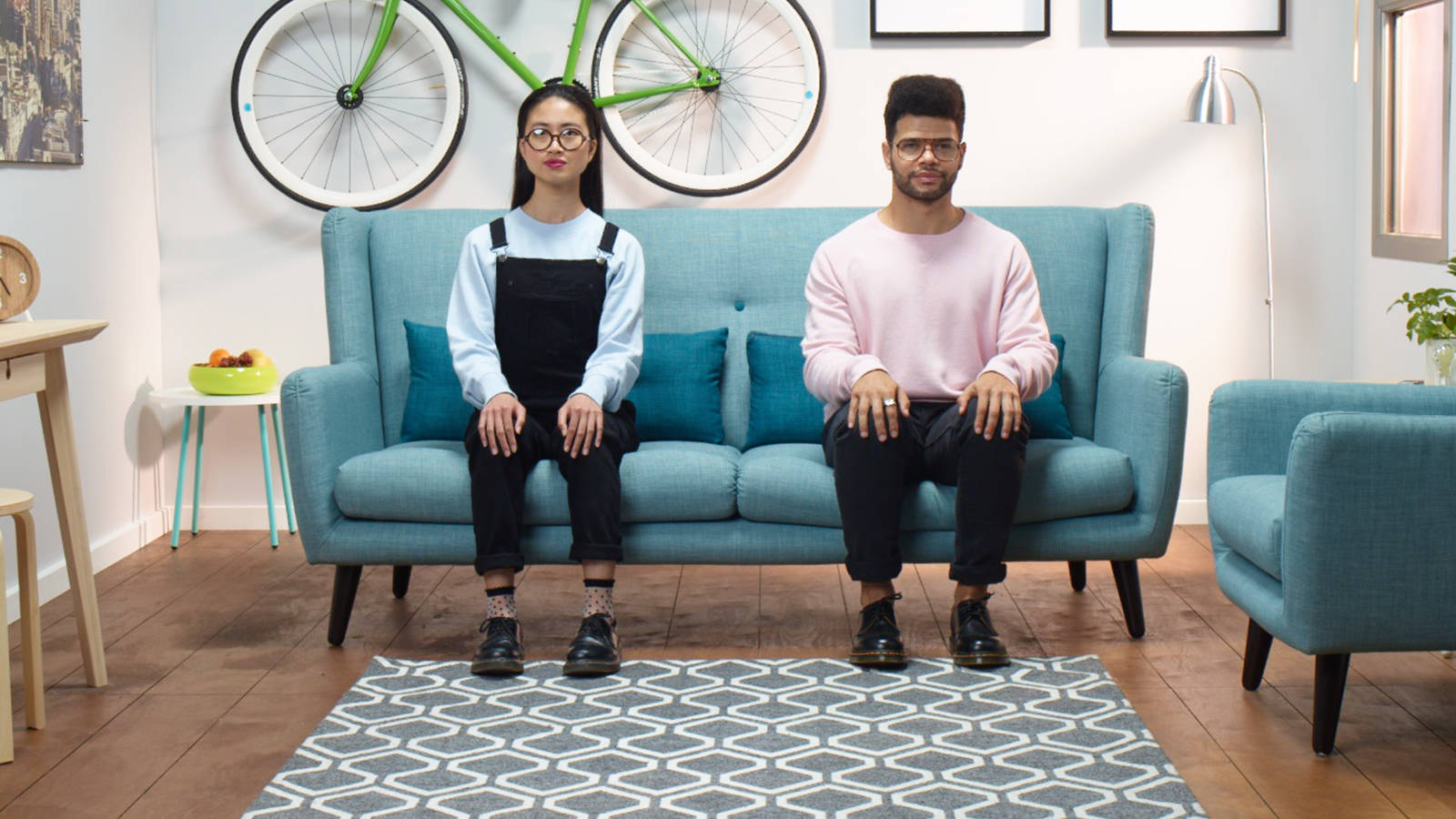 Couple sitting on blue fabric sofa