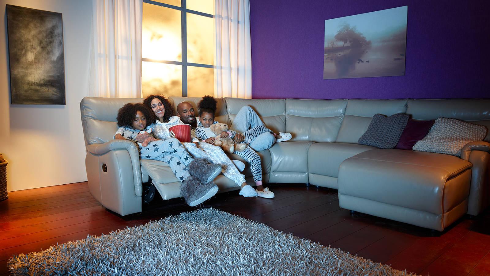 Family huddled on a white leather corner recliner sofa