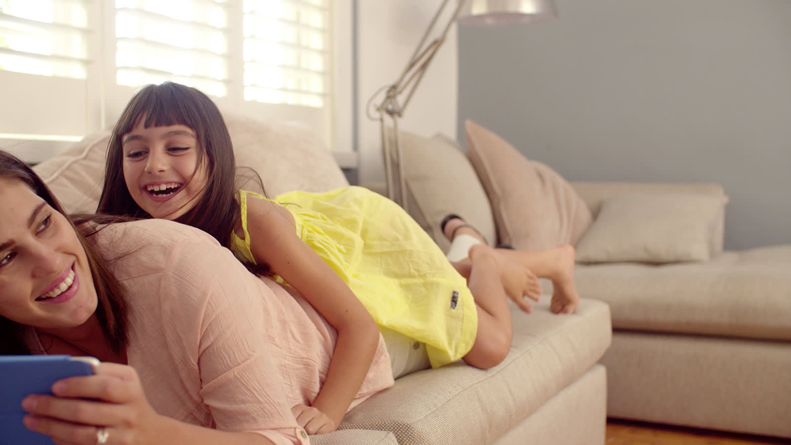Mother and daughter laughing on a sofa