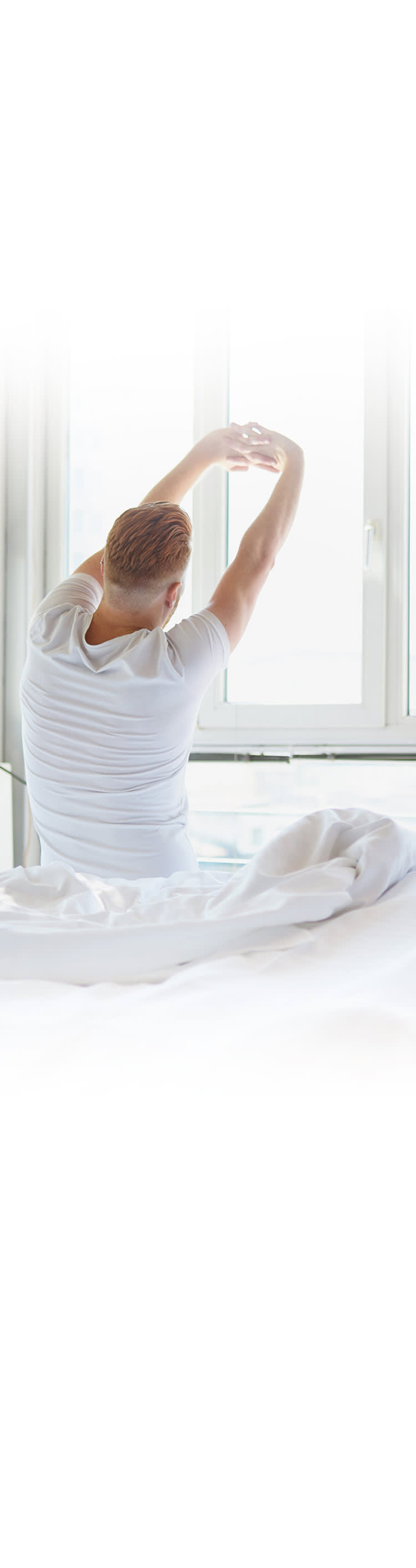 Man stretching as he gets out of bed