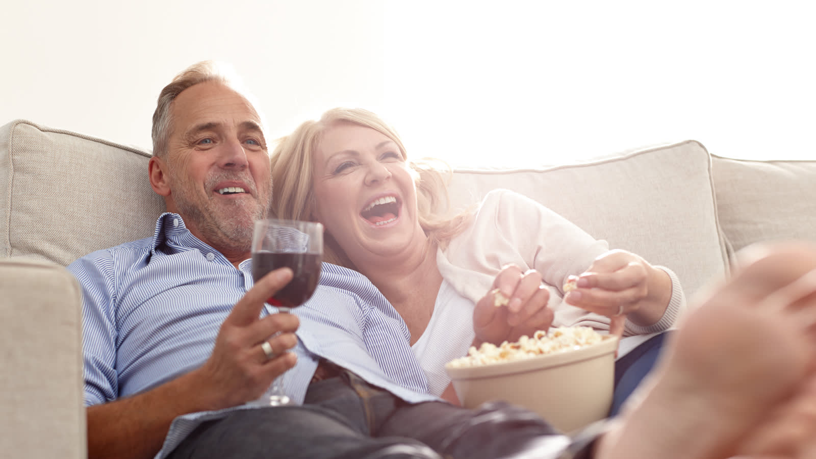 Couple drinking wine and eating popcorn on a white fabric sofa