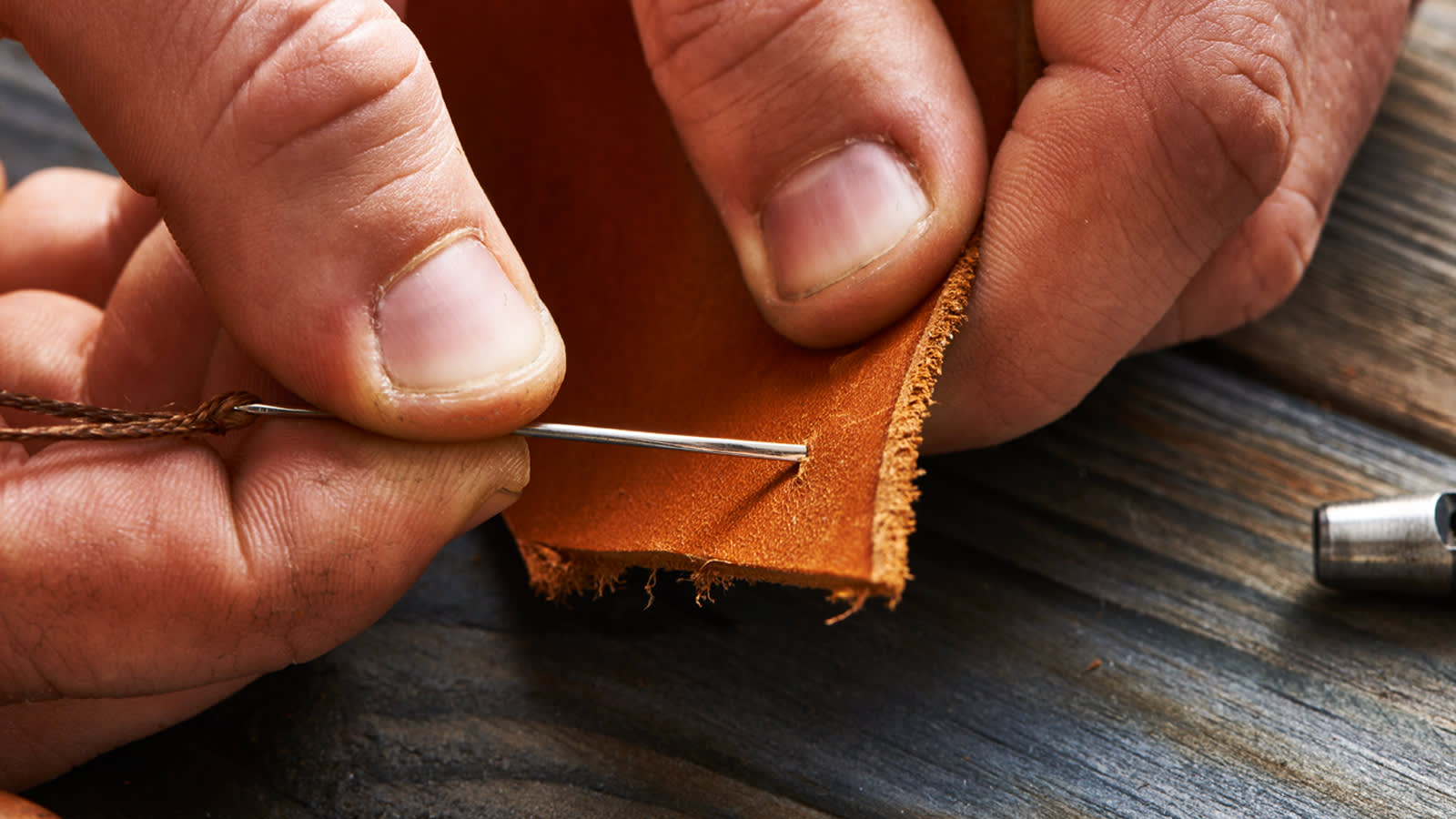Man hand stitching leather