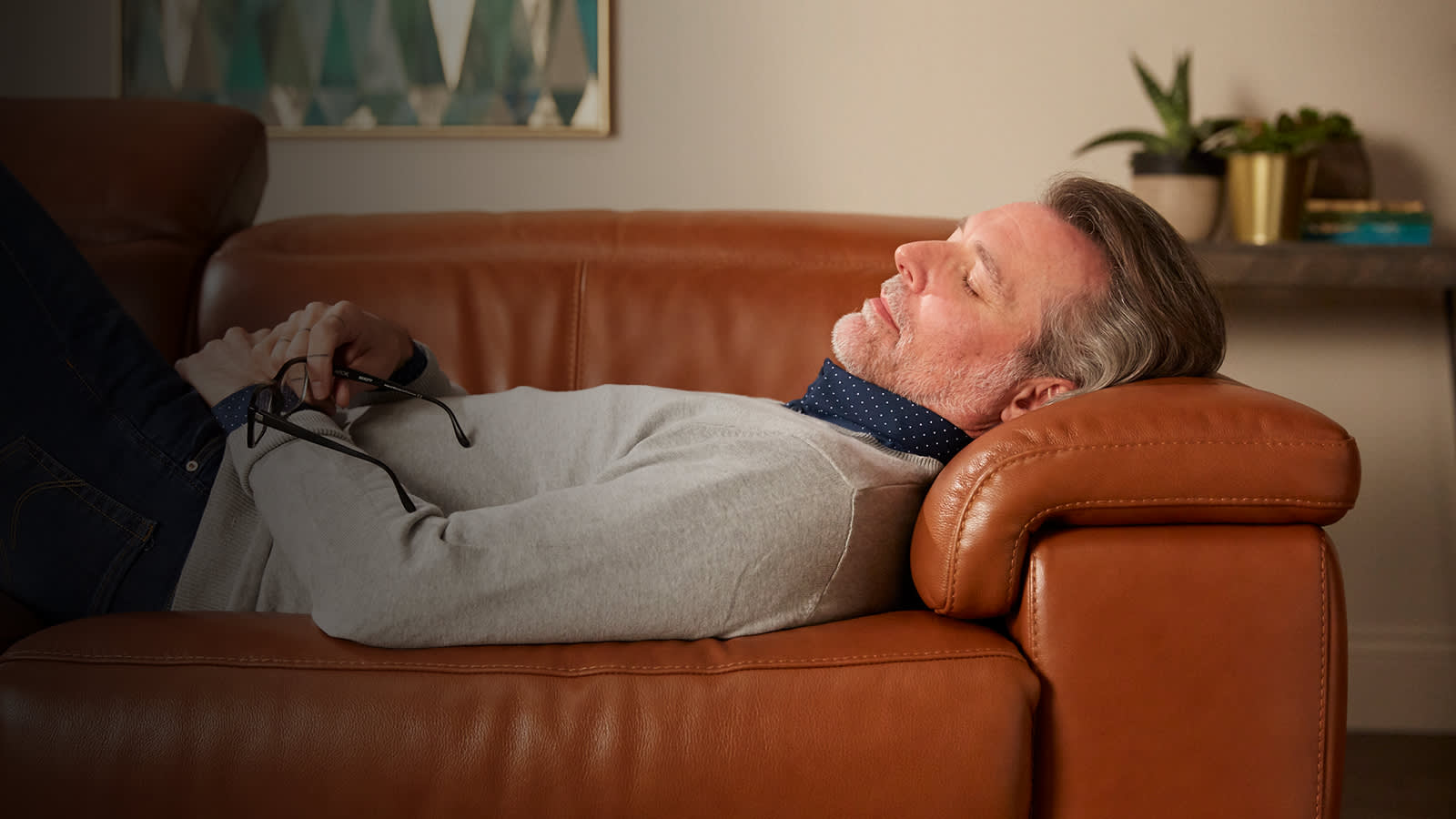 Man relaxing on brown leather sofa