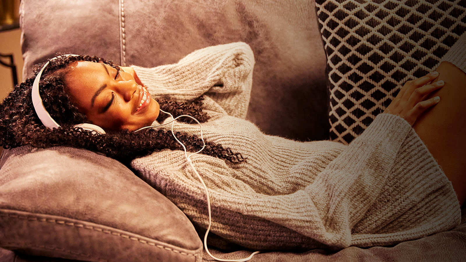 Woman relaxing on brown sofa listening to music
