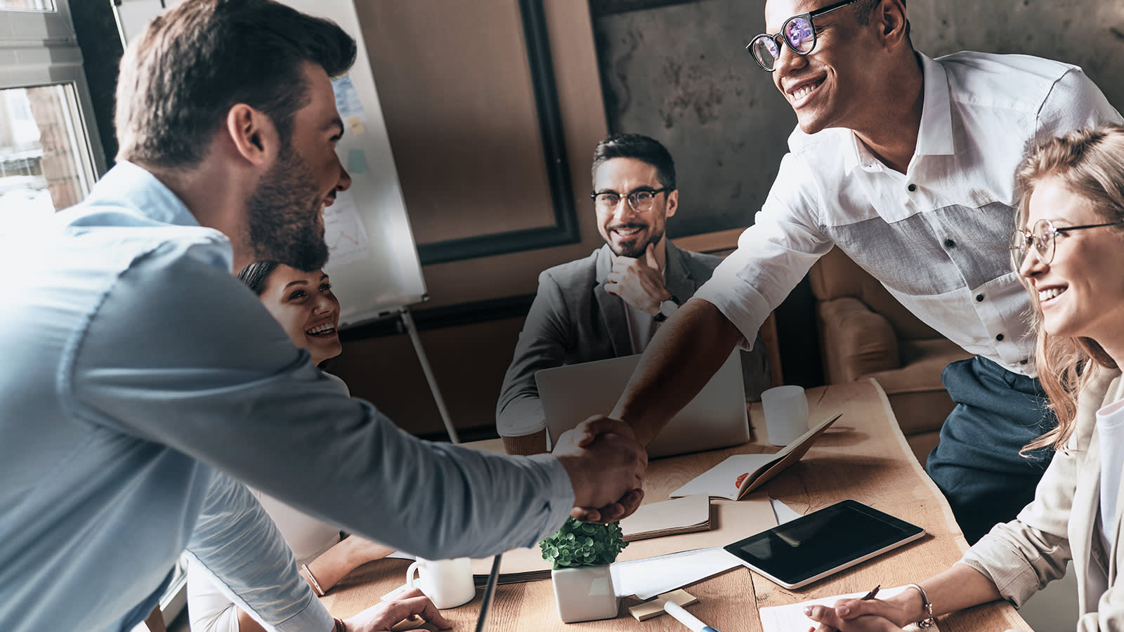 Men shaking hands in meeting