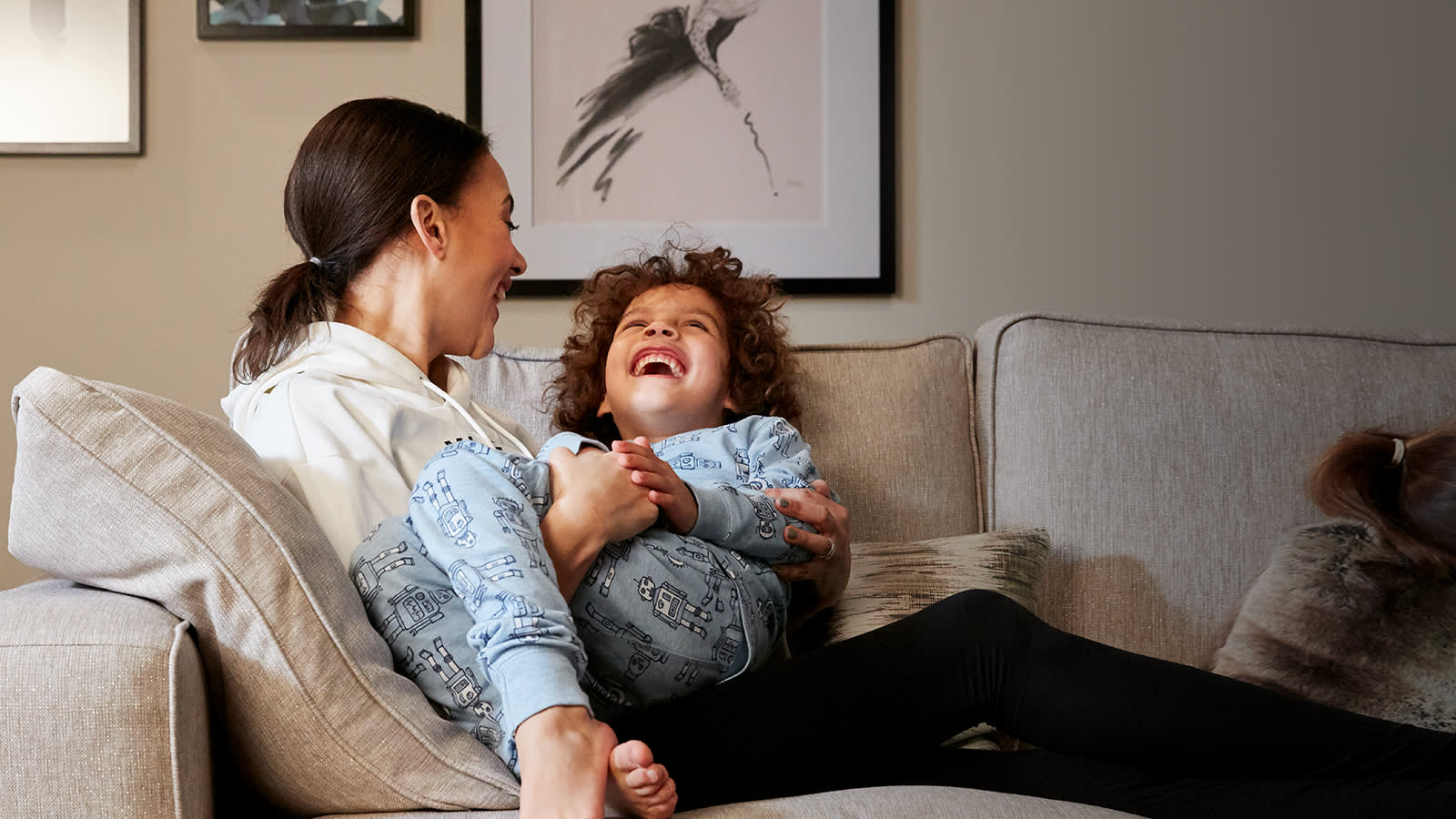 Mother and child laughing on a sofa