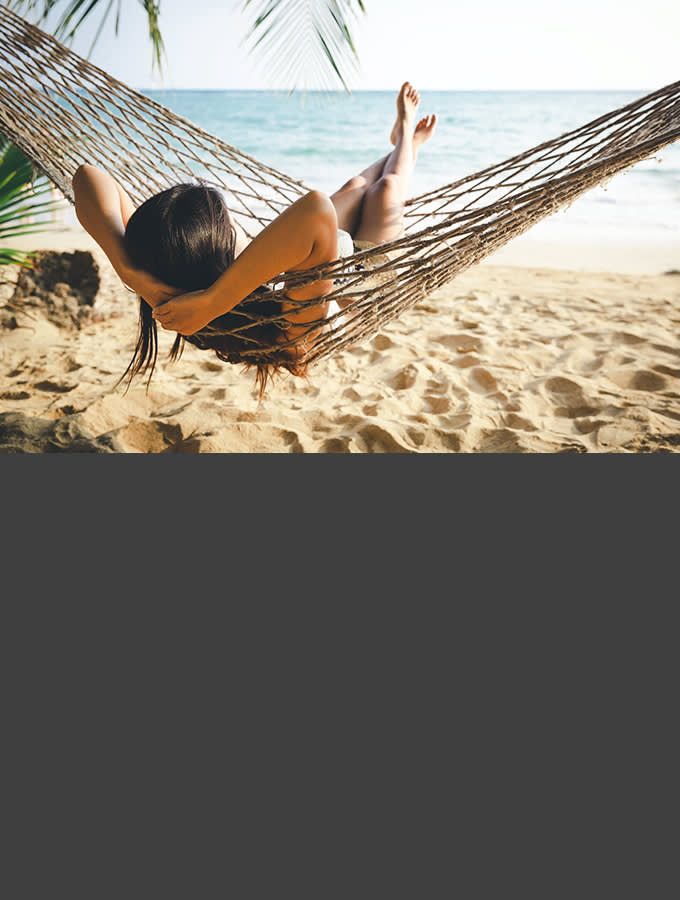 Woman relaxing in a hammock on a beach