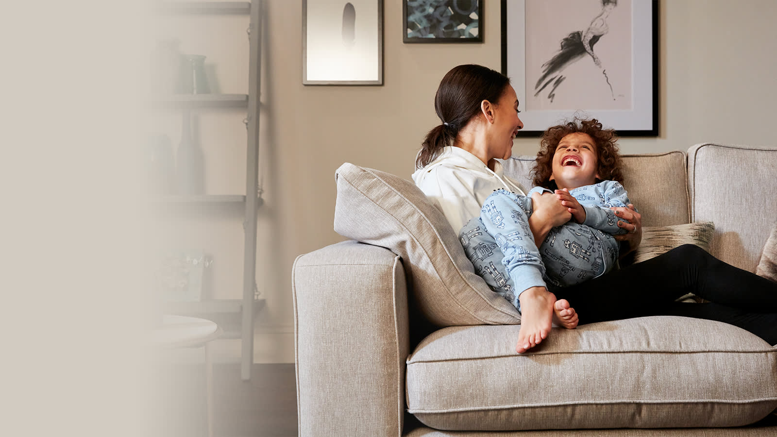 Mother and child laughing on grey fabric sofa