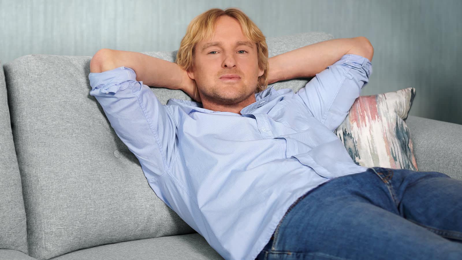 Owen Wilson relaxing on a Sofology Demure grey fabric sofa