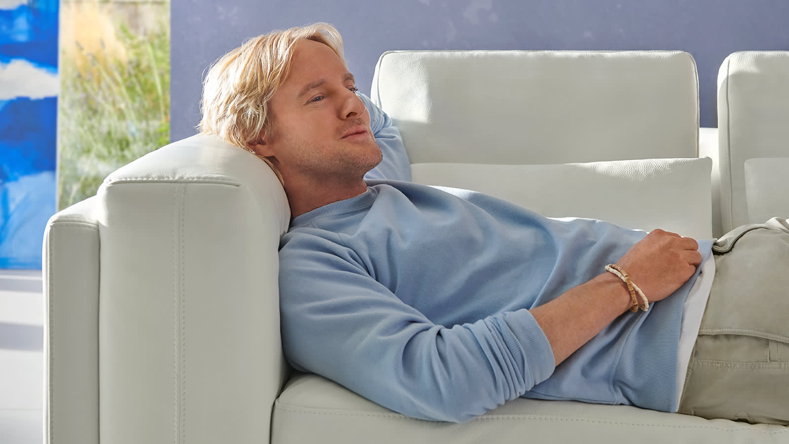 Owen Wilson relaxing on a Sofology Odessy white leather sofa
