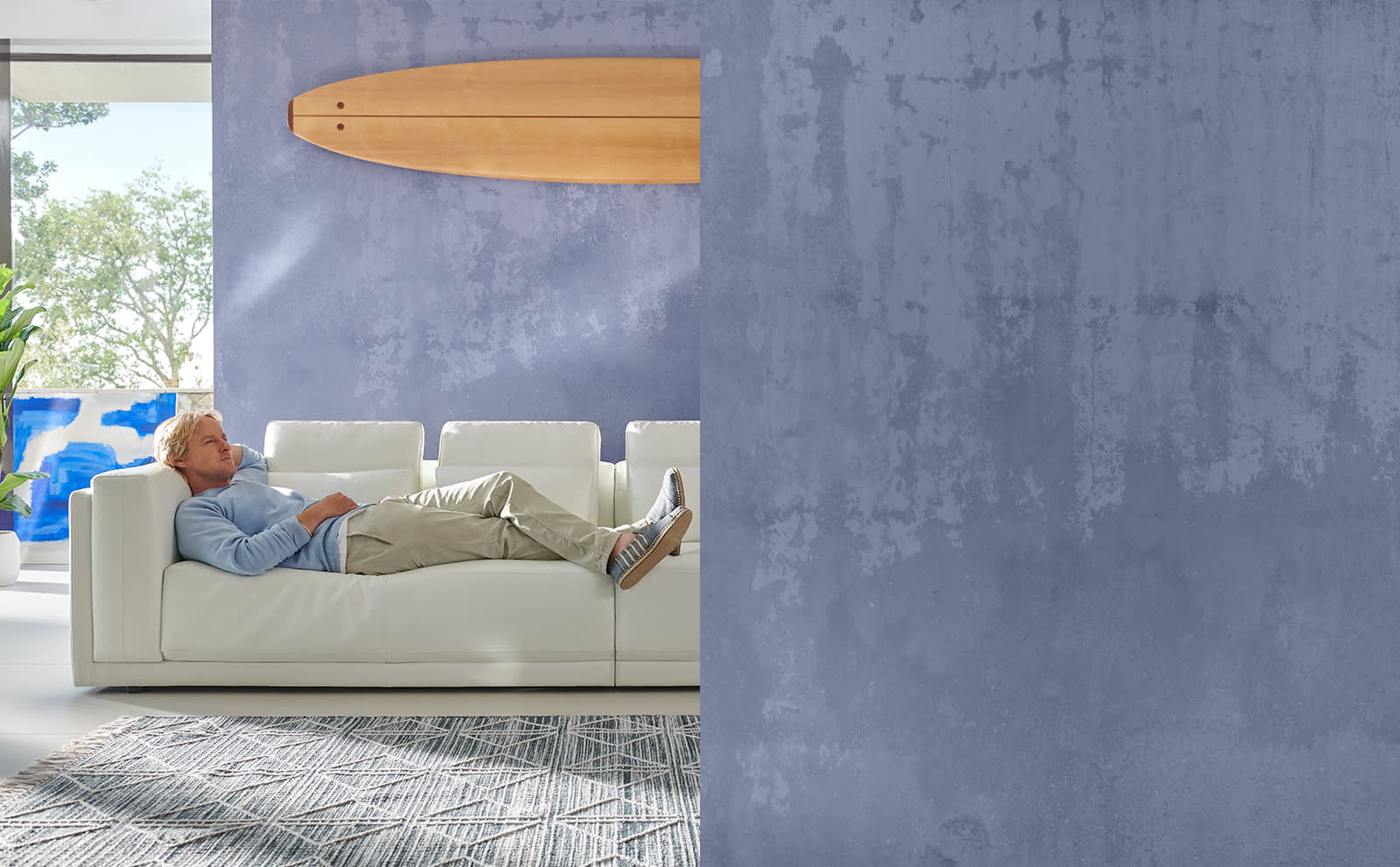 Owen Wilson lying on a Sofology Odessy white leather sofa
