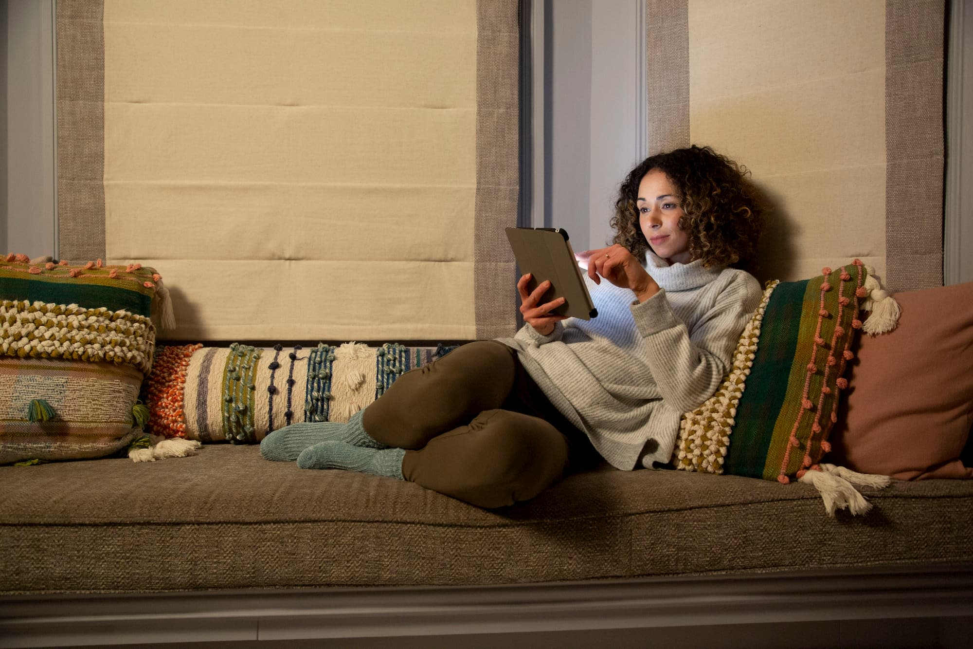 Woman sat on a sofa with a tablet